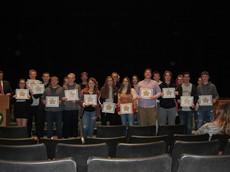 Dozens of high school students holding certificates