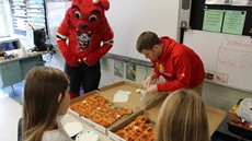 A man and dog mascot stand near two pizzas with two young girls
