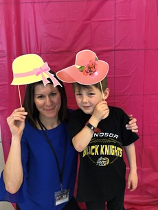 Woman posing with a child, each holding a picture of a hat on a stick