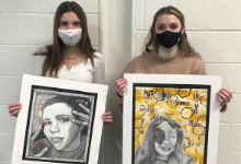 Two teenage girls in masks holding paintings