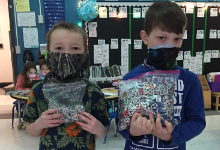 Two young boys in masks holding bags of can tabs