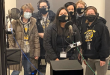 Six women wearing masks in front of microphones