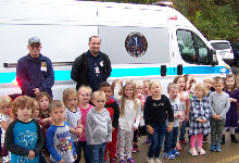 A group of small children standing wtih two men in front of an ambulance