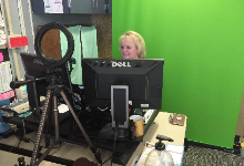 Eileen Mulcahy at a desk in front of a green screen
