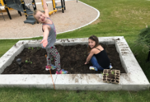 Two smiling young girls in a garden