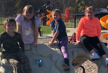 Four young children sitting on a playground structure