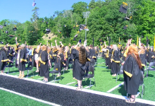 Dozens of people in black caps and gowns on a football field