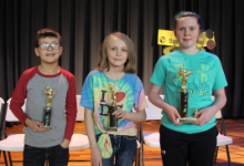 A boy and two girls each holding a trophy