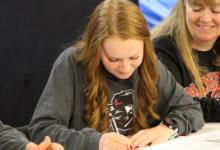 Bailey Morgan signs a piece of paper