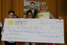 Two children and a woman holding a big check