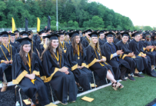 Rows of high school students in caps and gowns