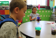 A boy looking down at a cup of dirt