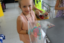 A young girl holding a plastic bag with a colorful clay creature in it