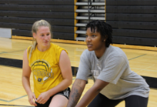 Two young women kneeling on a basketball court