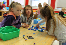 Three young girls at a table working with Lego