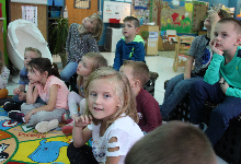 A group of young children sitting on a rug in a classroom