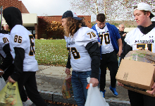 Teenagers in football jerseys carrying bags and boxes