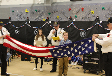 Two men folding an American flag with a boy standing between them