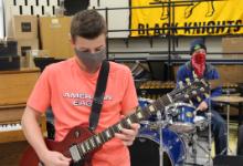 Max Baxter holding a guitar