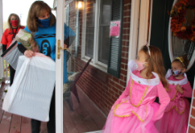 Two women in crayon costumes open a door to two young girls in princess costumes
