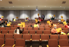 Teenagers in auditorium holding up yellow envelopes