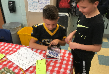 Two young boys looking at a book on a table