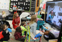 Kindergarten students looking at large screen