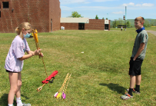 Girls with Atlatl and boy watching