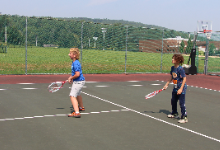 Two young boys playing tennis