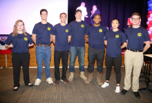 Seven young men and women standing in matching blue shirts in front of a stage