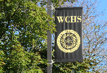 WCHS Black banner in front of a tree