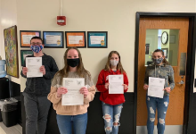 4 students holding certificates