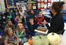 A group of young children sitting in front of a woman who has pumpkins to her side