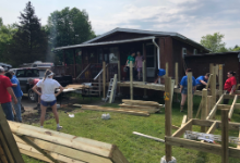 A structure under construction behind a home with people standing around
