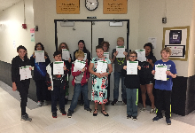 13 students holding certificates in a hallway