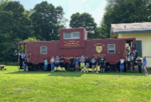 Teenagers standing in front of a train car outside