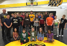 Over a dozen children standing on a wrestling mat smiling