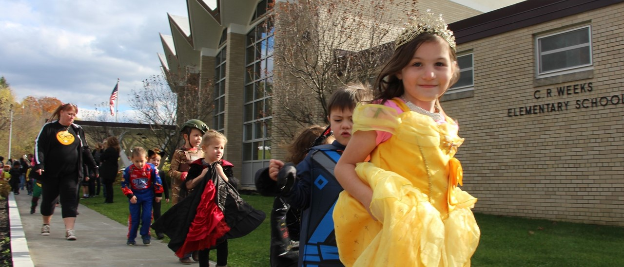 elementary school girl in a yellow princess dress walking outside with other students in costume behind her