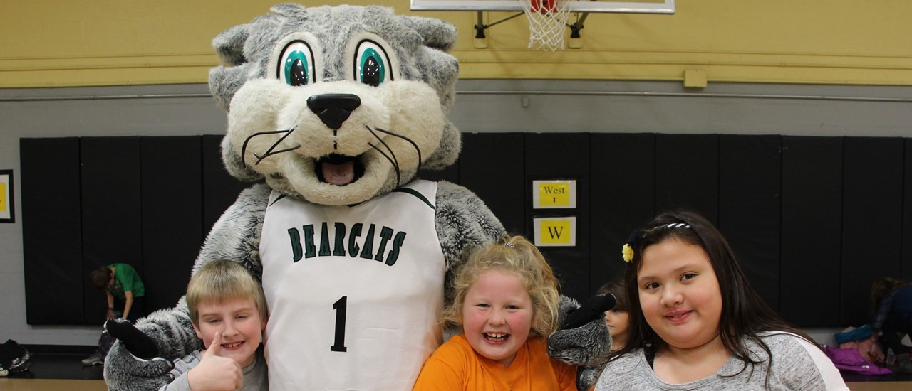 Baxter the Bearcat mascot with his arm around a young boy giving a thumbs up sign and two other young girls on the right of the picture