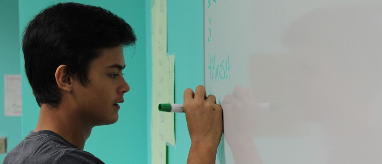 Male high school student writing with a marker on a white board