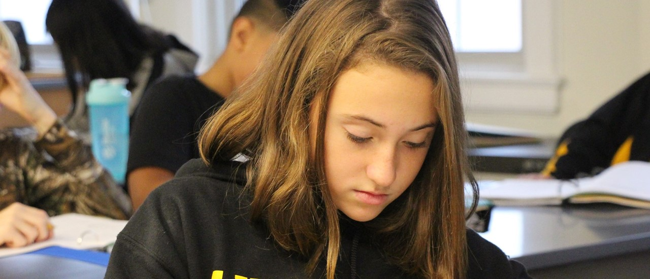 Middle School female student in black Windsor Field Hockey sweatshirt looks down at her desk with a pencil in her hand