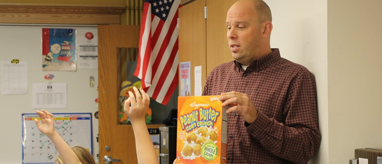 Teacher holding up a cereal box in the front of the class with hands raised in front of him