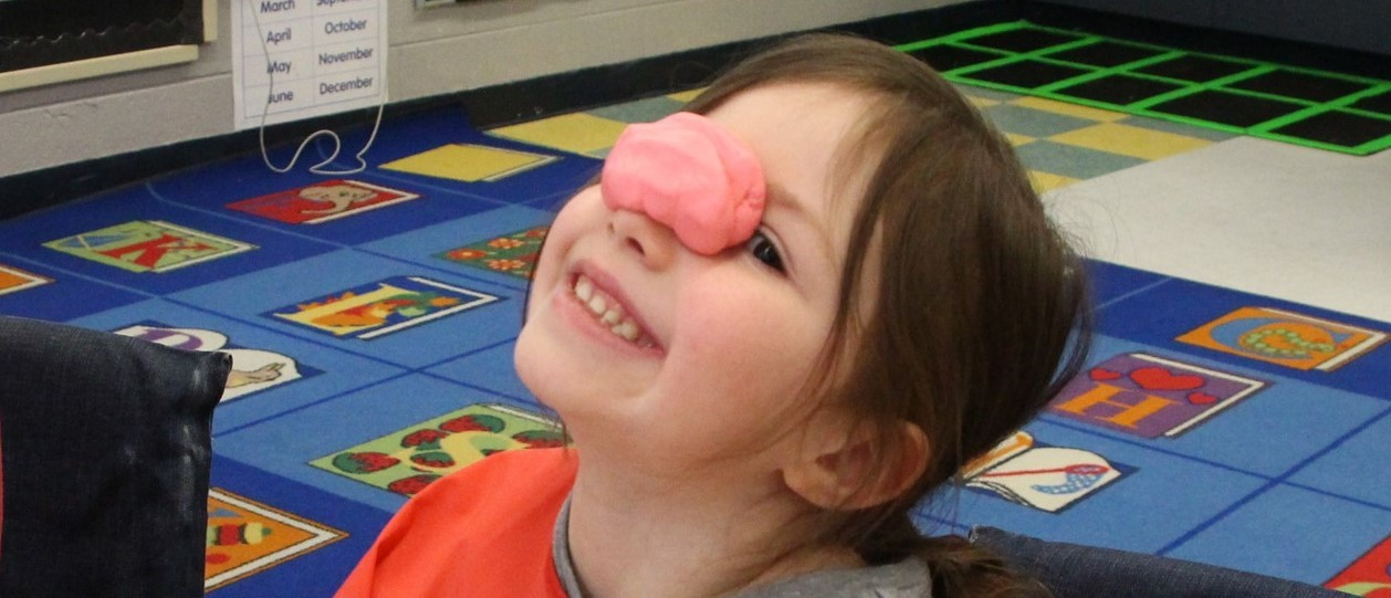 Little girl with Play-doh on her nose