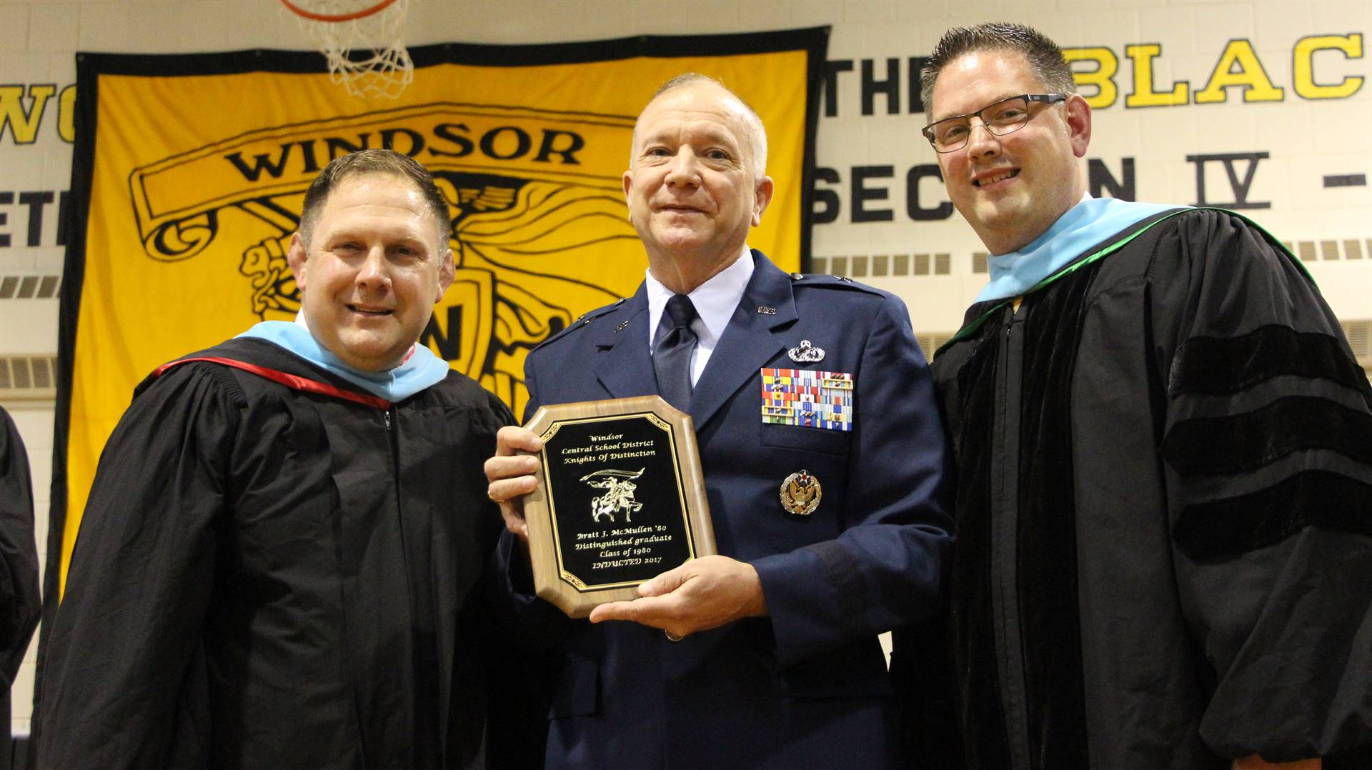 General McMullin holding a plaque between Chris Durdon and Jason Andrews