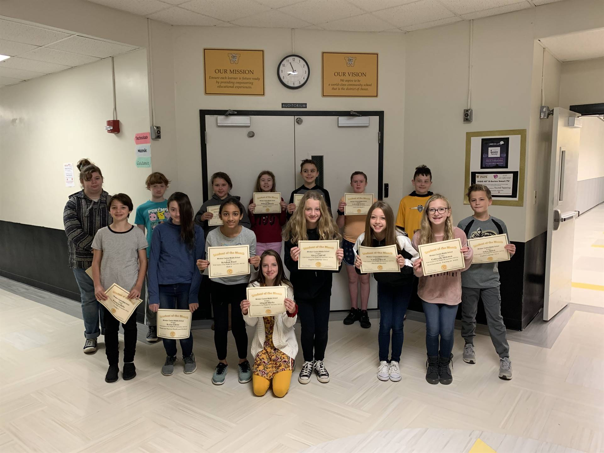 15 6th graders holding certificates in a hallway