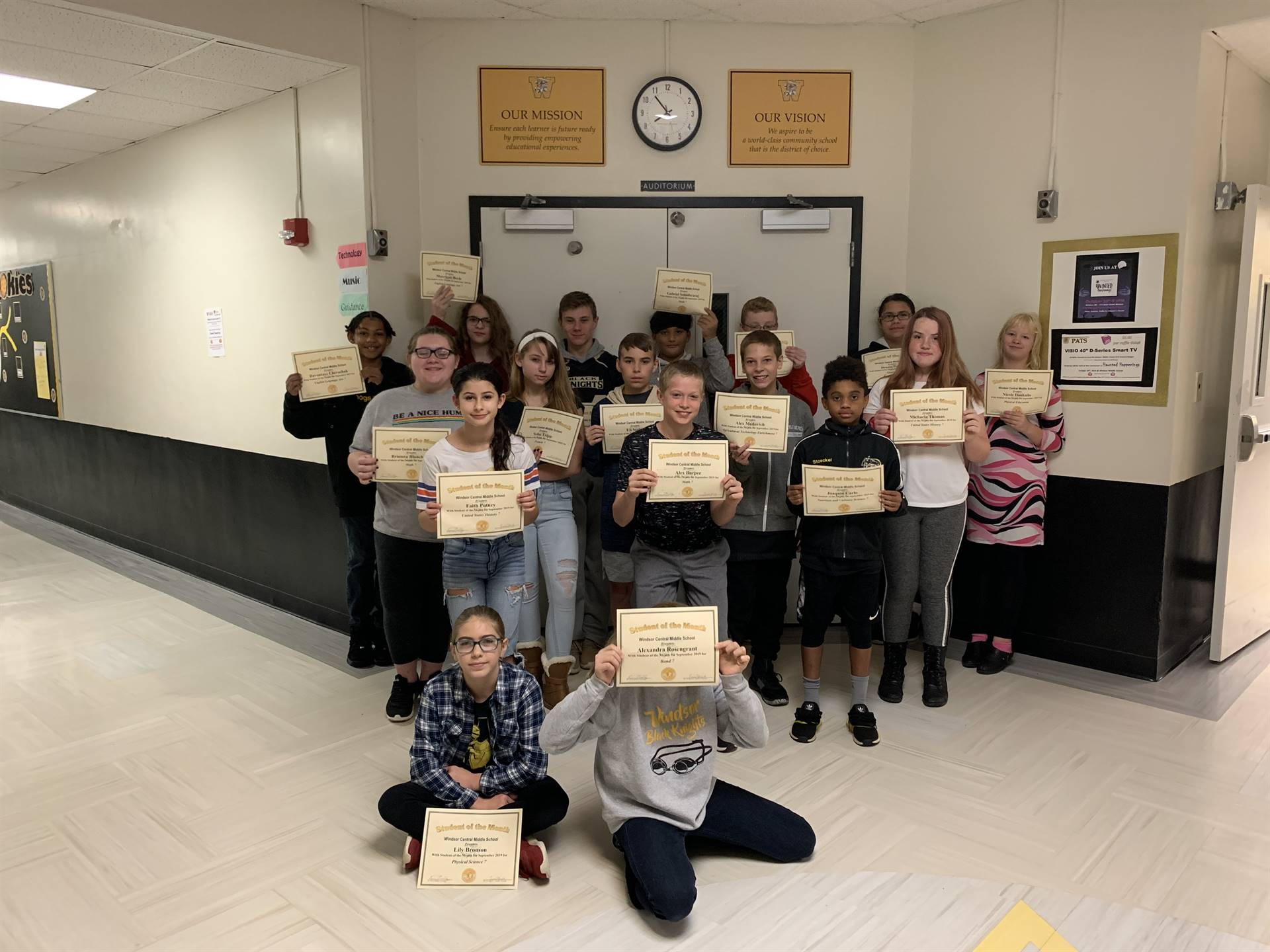 17 7th graders holding certificates in a hallway