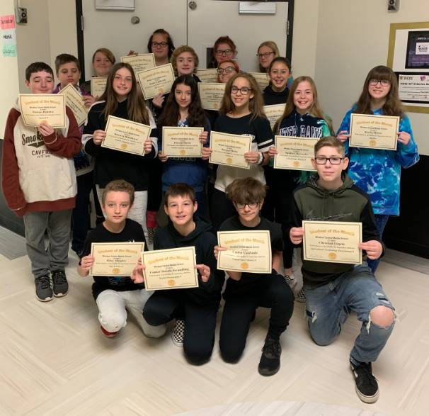 16 8th graders holding certificates in a hallway