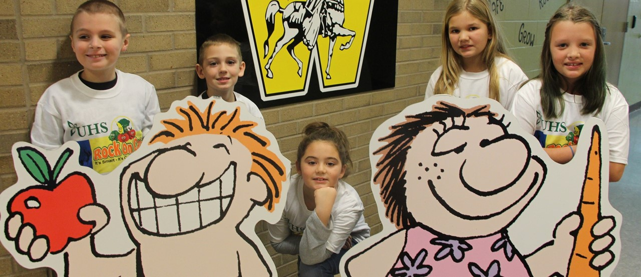 Five elementary students behind cutouts of animated characters