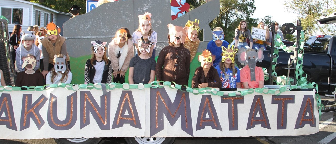 students in costume behind a hakuna matata banner