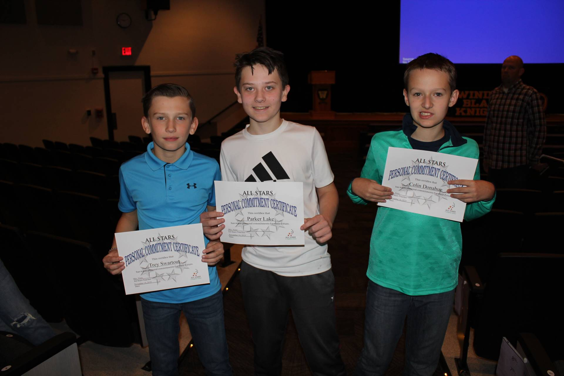 Three boys holding certificates